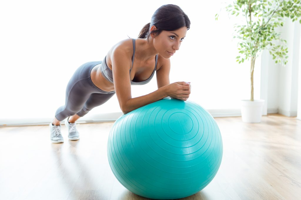 Portrait of beautiful young woman doing pilate exercise with fitness ball at home.